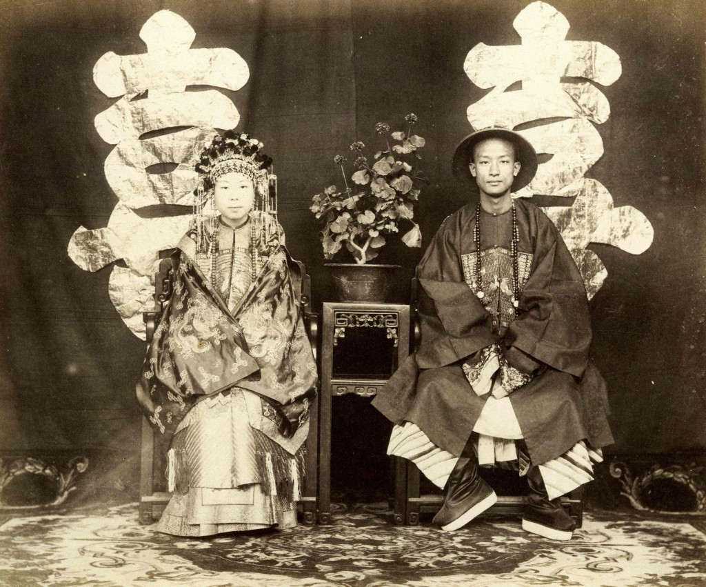 A portrait of a bride and groom in front of a studio screen with chinese lettering.
